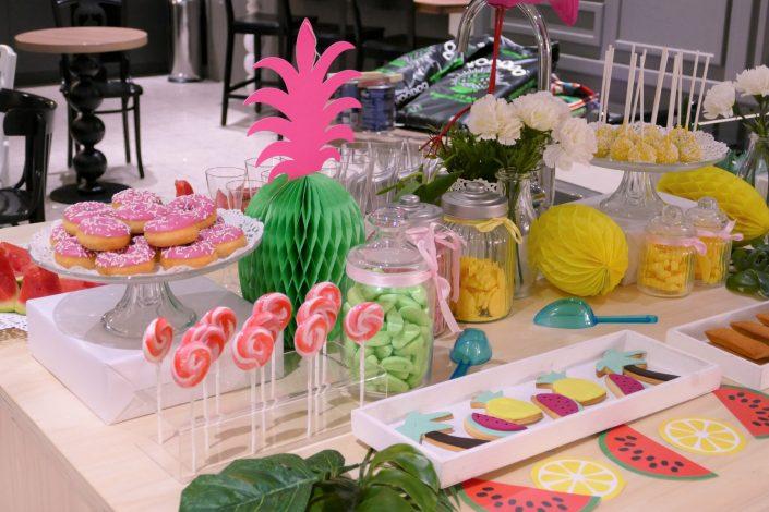 Table tropicale pour Adagio par Studio Candy - donuts roses à la fraise, sucettes, sablés décorés, bonbons et cake pops jaunes