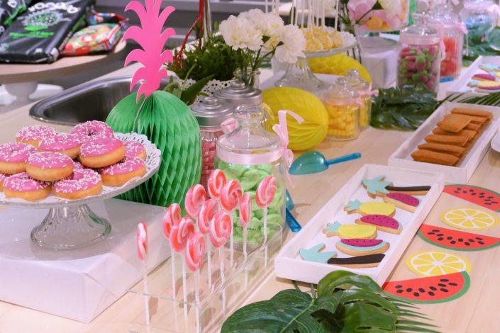 Table tropicale pour Adagio par Studio Candy - donuts roses, sucettes, sablés décorés, ananas, pastèque, palmier et bonbons