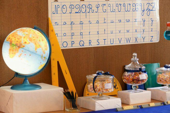 Sweet table back to school par Studio Candy pour Kering - globe terrrestre, règle jaune, colliers de bonbons, sucettes