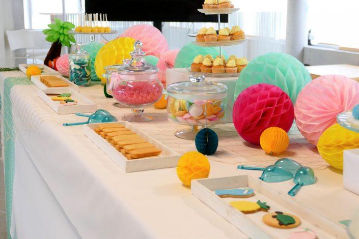 Bar à pâtisseries par Studio Candy pour L'Oréal - cake pops bleus, bonbons soucoupes, sablés décorés ananas, tongs, tortue, cupcakes