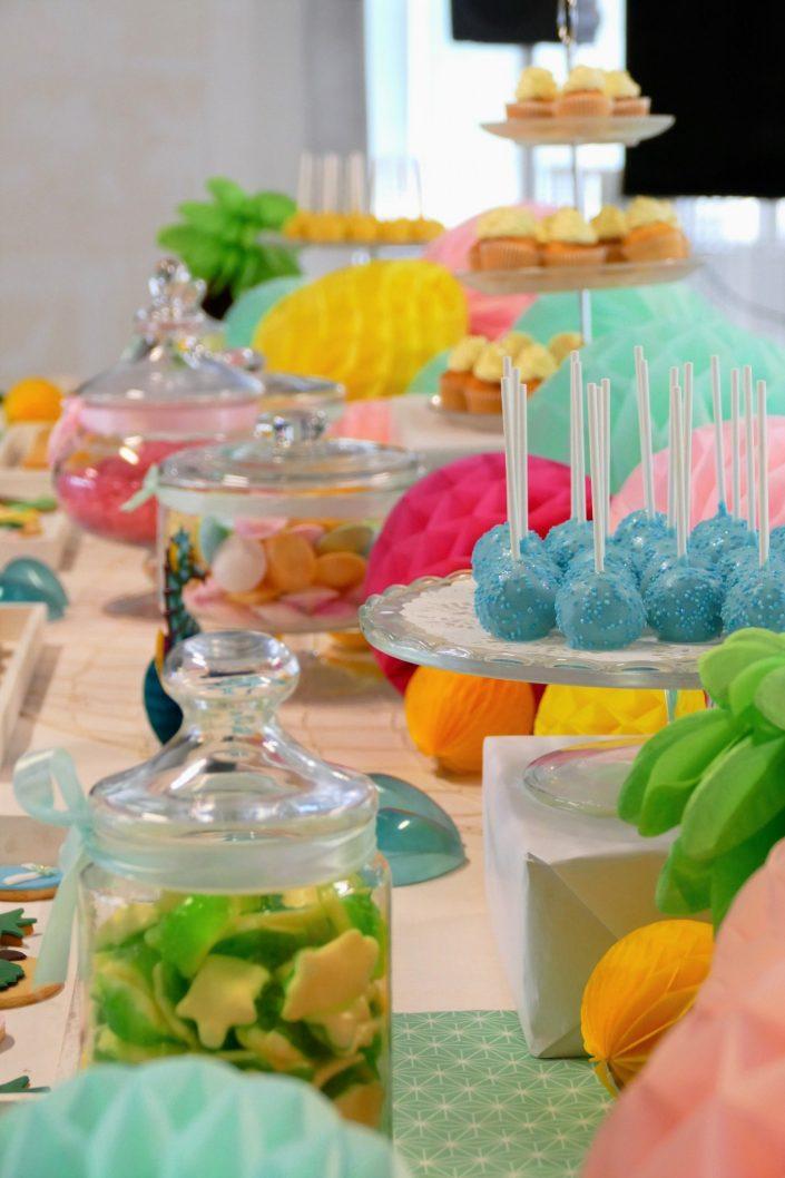 Bar à pâtisseries par Studio Candy pour L'Oréal - cake pops bleus, soucoupes, sablés décorés tongs, tortue, ananas, cupcakes