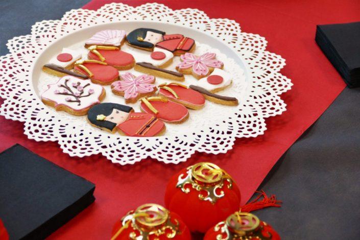 Goûter thème Asie pour Chronopost par Studio Candy - Sablés décorés tongs, geisha, drapeau japonais et chinois, lanterne, dragon, enventail, fleurs de cerisiers, cake pops au chocolat, financiers amande, décoration et scénographie personnalisée Asiatique
