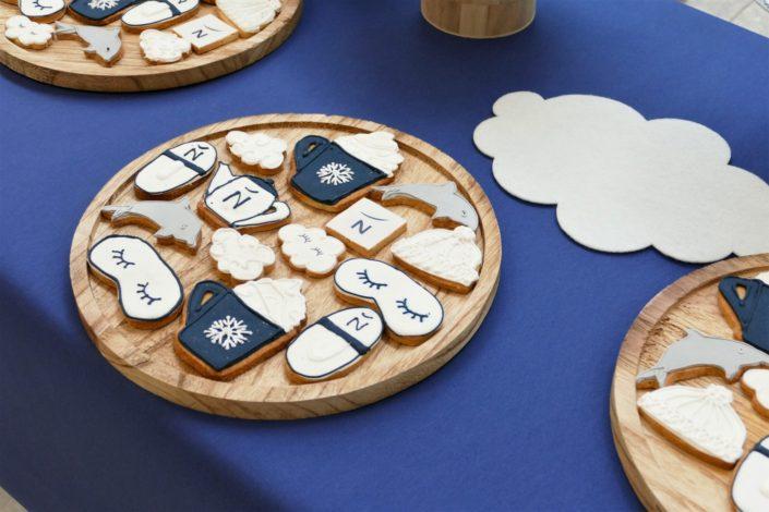 Bar à pâtisseries personnalisés pour la nouvelle carte graphique Novotel au siège d'Accor - sablés décorés masque de nuit, théière, nuage, chausson d'hôtel, chocolat chaud
