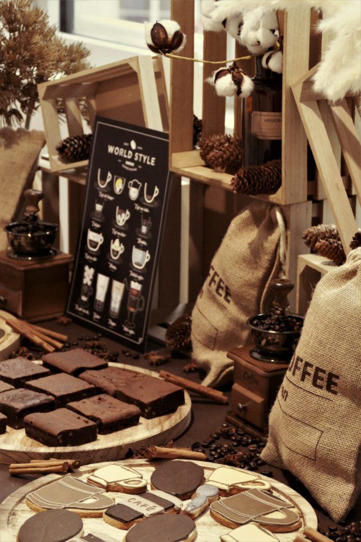 goûter thème café avec décoration, sacs de jute, grains de café, cannelle, vases fleurs de coton, financiers amande, brownie, donuts chocolat, sablés décorés
