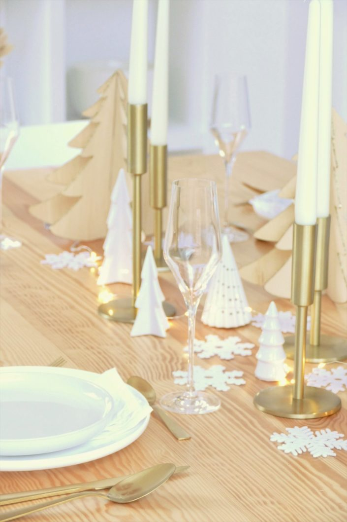 Table de Noël ambiance Laponie avec assiettes en céramique blanche, serviettes en lin blanc, flocons de neige, sapins en bois, bougeoirs dorés, fleurs séchées, couverts dorés mat