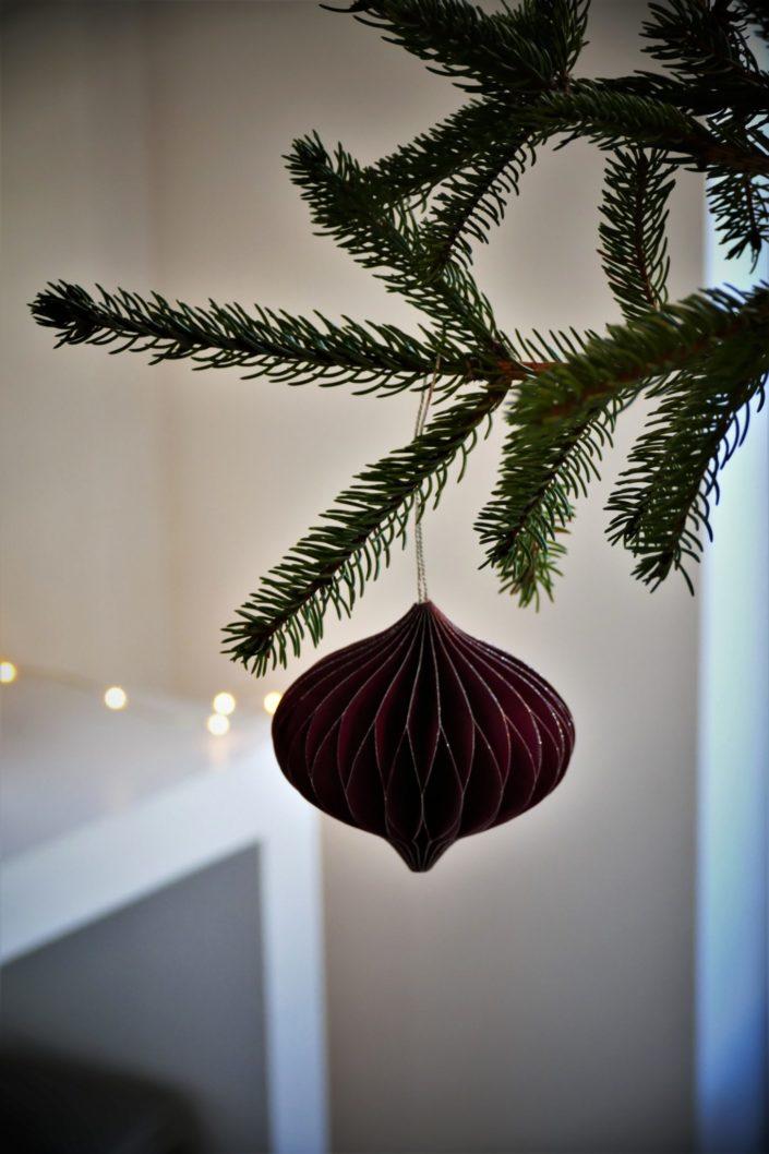Table de Noël ambiance sous bois réalisée par Studio Candy pour For Me Lab - assiettes noir mat, bols dorés brillant, serviettes en lin, branches de sapin, boules de Noël en papier, pommes de pin