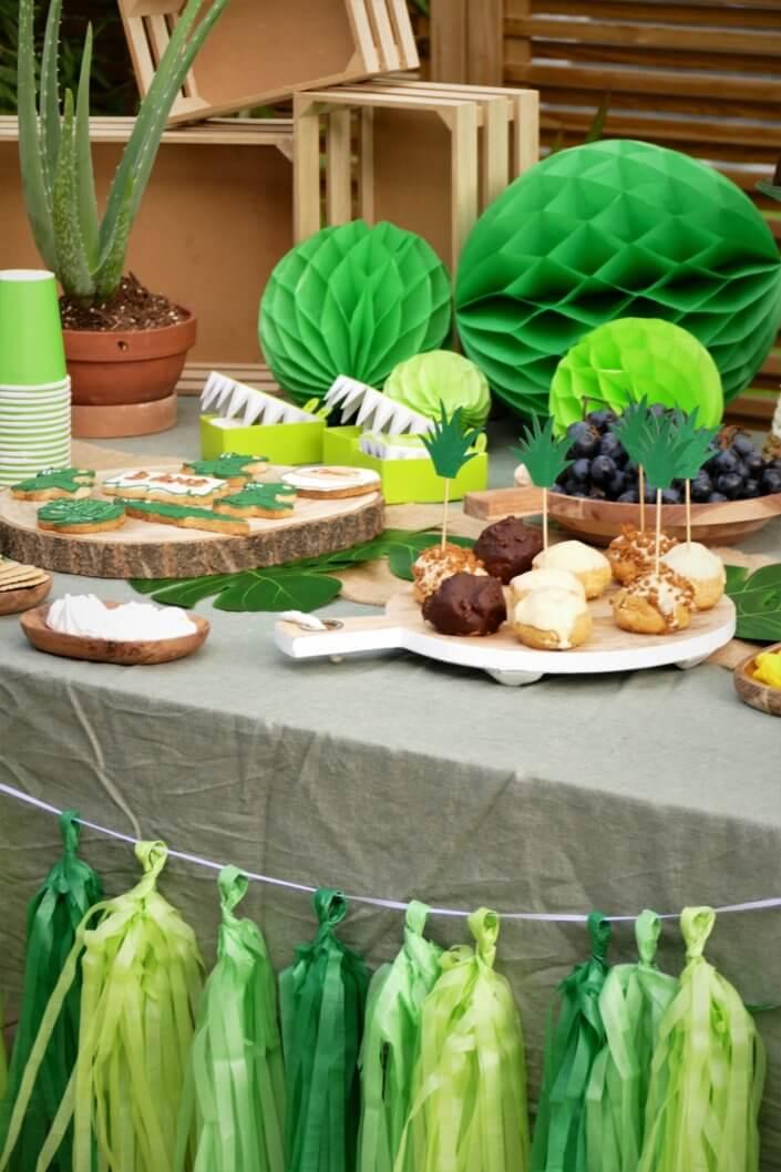 Anniversaire crocodile jungle avec sablés décorés , petits choux farcis, raisins, financiers amande, gâteaux au chocolat, bonbons. Décoration verte, feuilles tropicales monstera, boîtes crocodiles, vases, guirlande et ballons hélium.